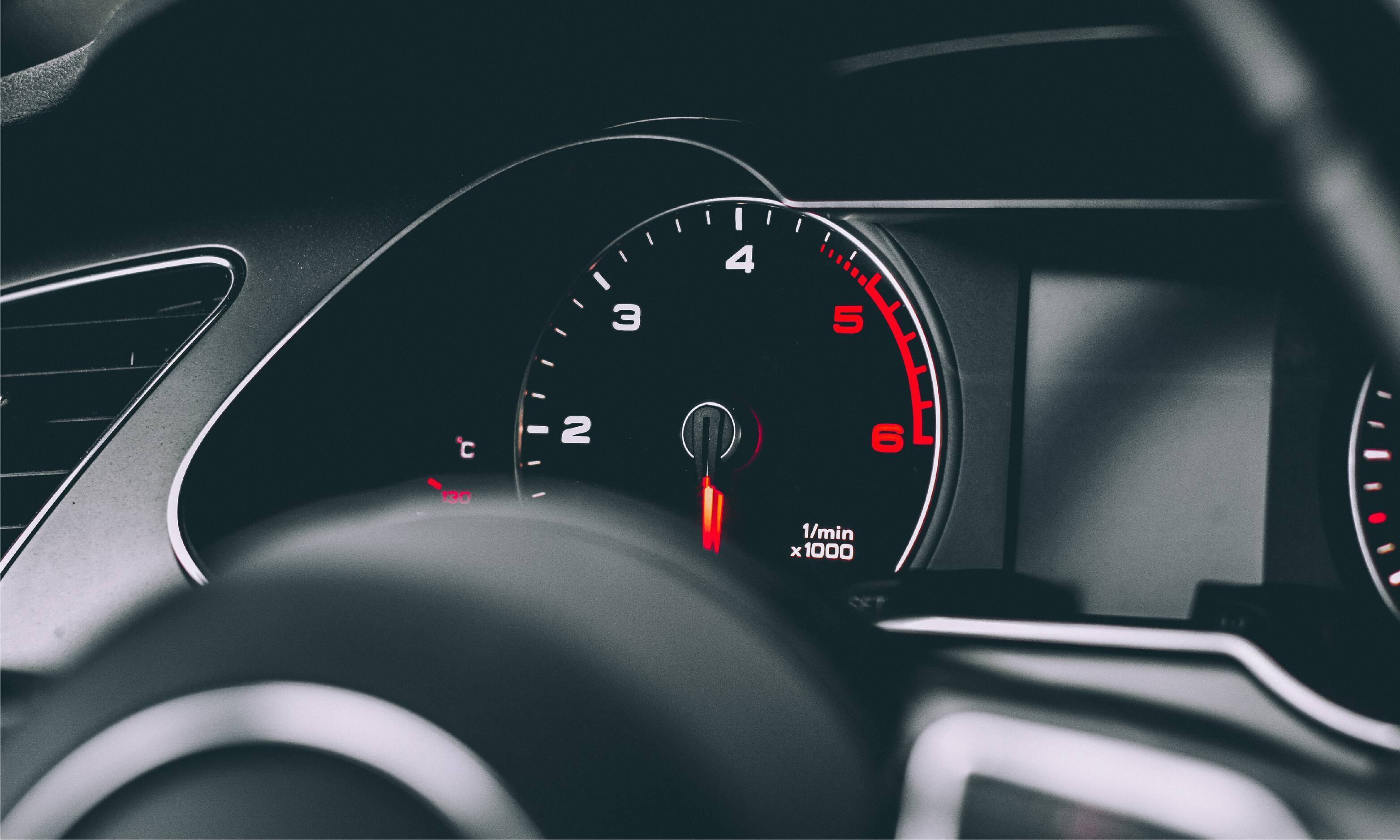 Photo of a tachometer on a car looking through the steering wheel