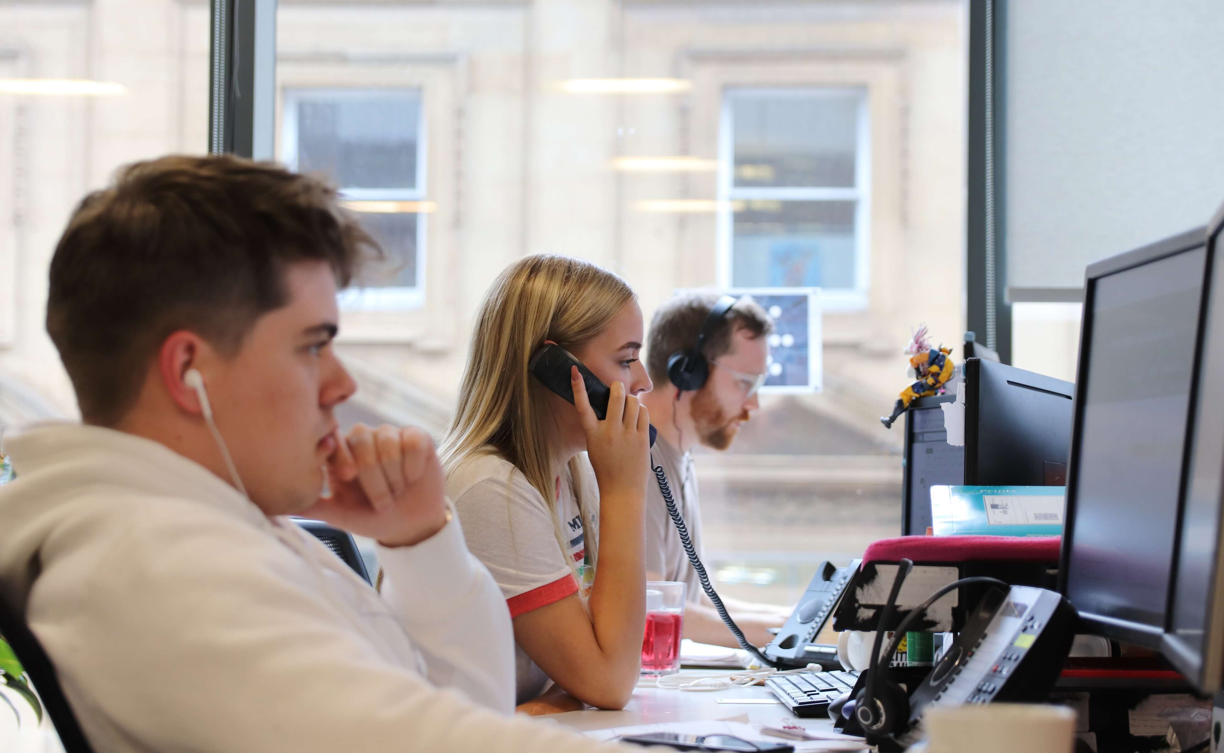 A photo of three recruitment consultants working at their desks