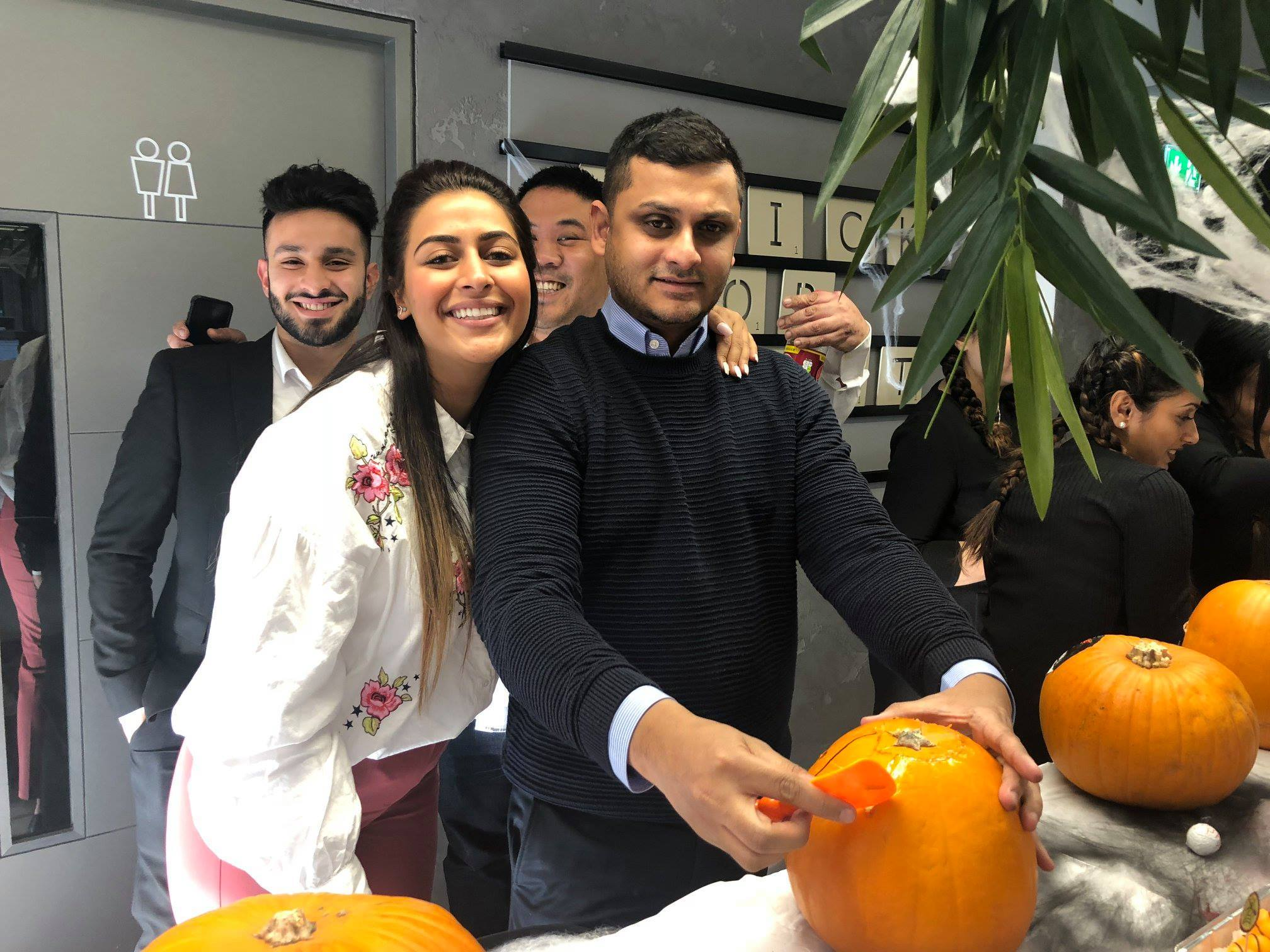 A group of InterQuest Group employees taking part in pumpkin carving competition at the London office