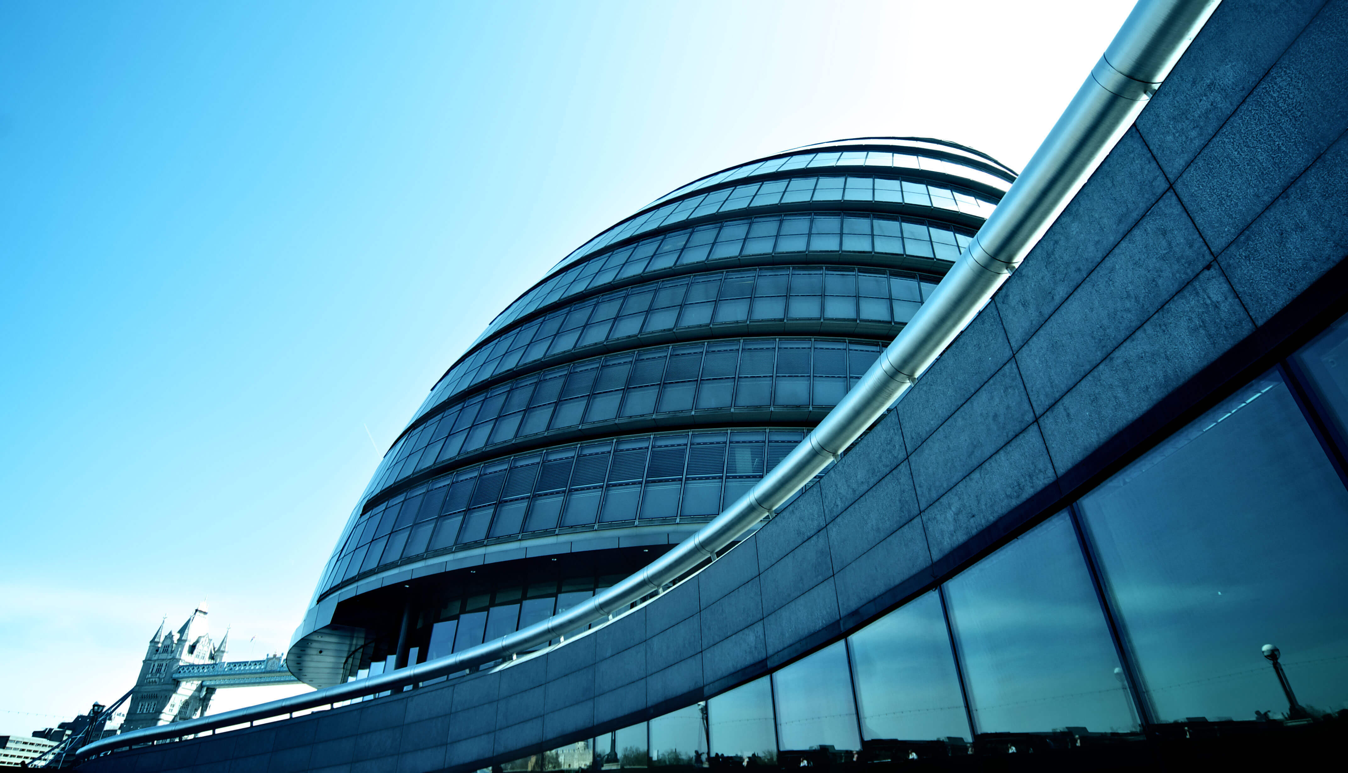 A photo taken at street-level of a dark grey building with floor-to-ceiling windows, clear blue sky