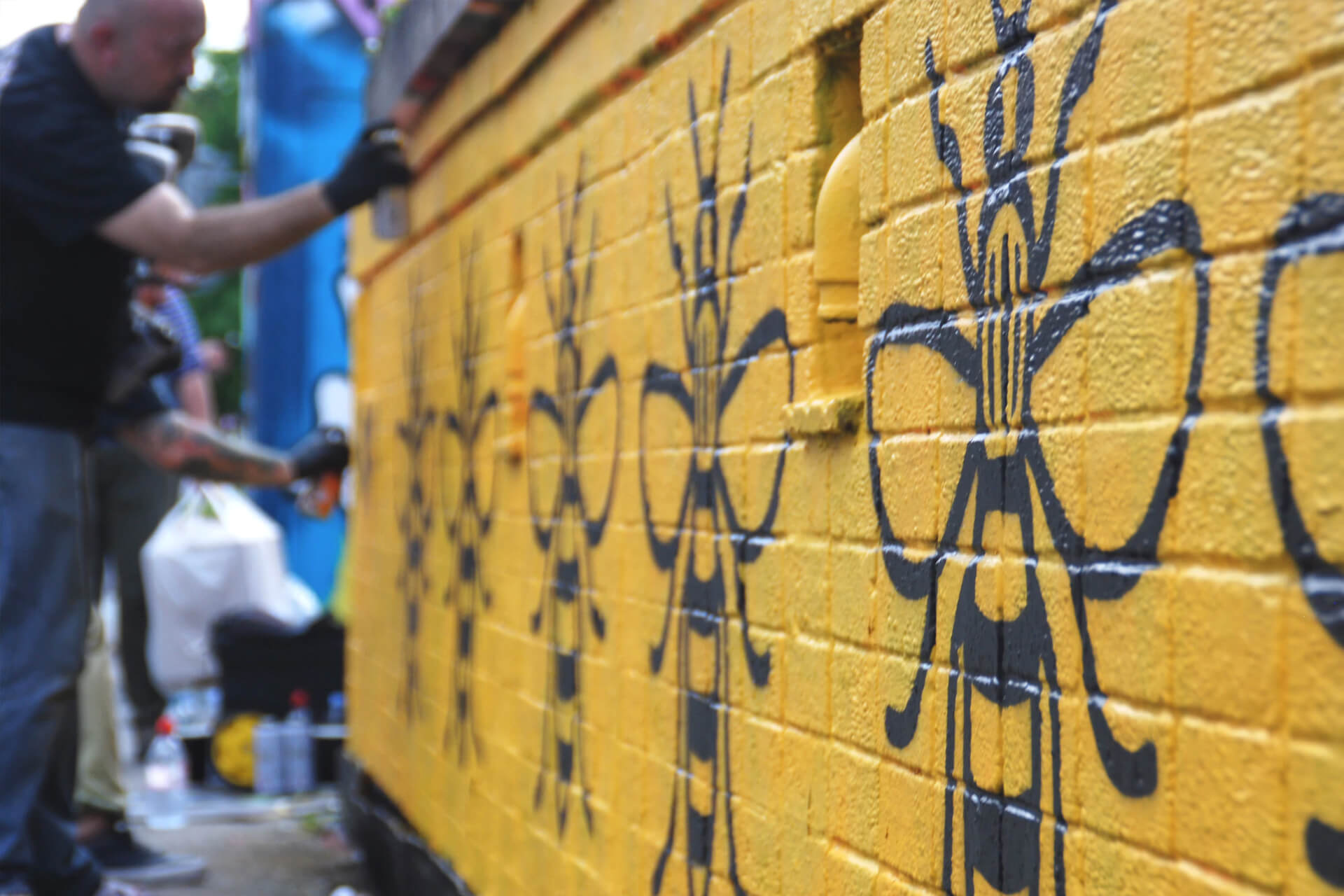 A yellow wall with the 'Manchester Bee' symbol painted on it multiple times
