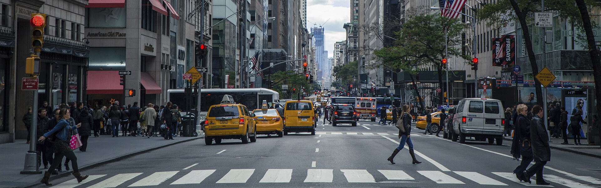 Photo from New York City street level people crossing the road yellow taxis