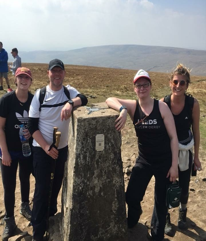 A photo of InterQuest Group colleagues at the top of a Yorkshire Peak