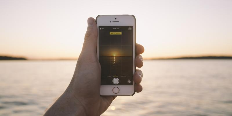 holding an iPhone taking a picture of a sunset on holiday